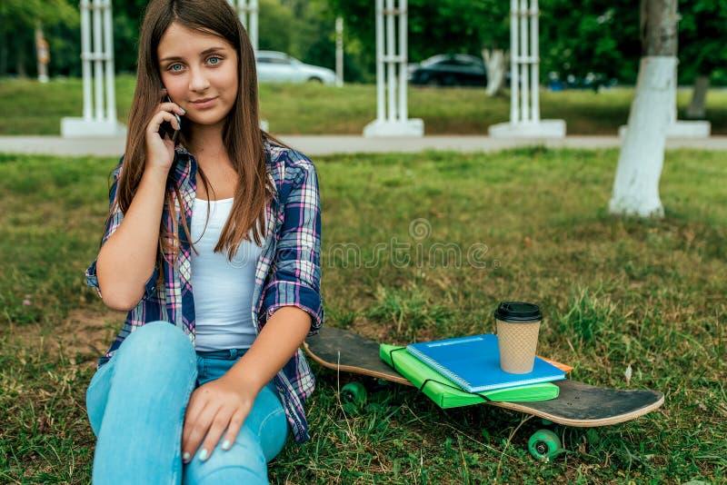女孩女小学生,学生坐公园绿草城市的13-16岁 在手上给圆环父母打电话 在水平以后的休息 图库摄影