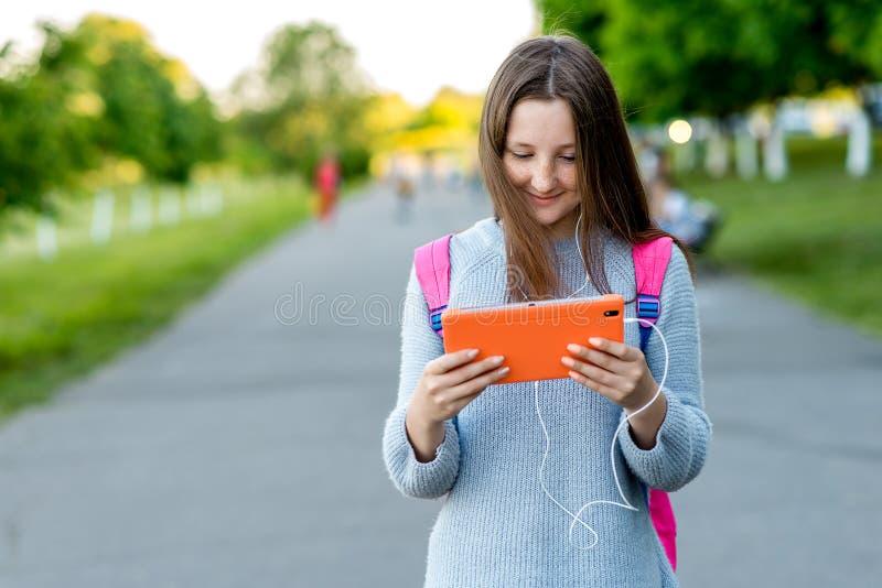 女孩女小学生 夏天本质上 拿着在他的背包后的手一种片剂 文本的空位 概念  免版税库存照片