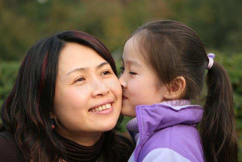 女孩她亲吻小母亲 库存图片