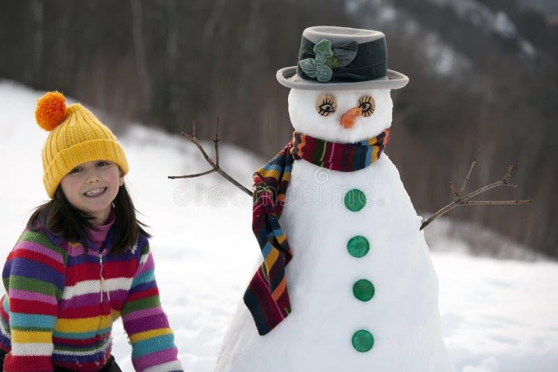 女孩她摆在的雪人 免版税图库摄影