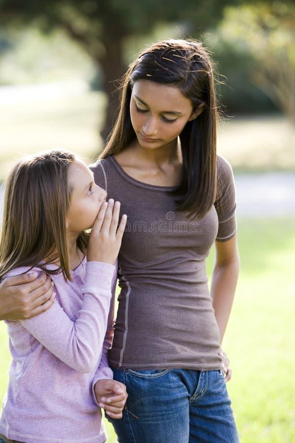 女孩她的更老的姐妹少年对耳语 免版税库存照片