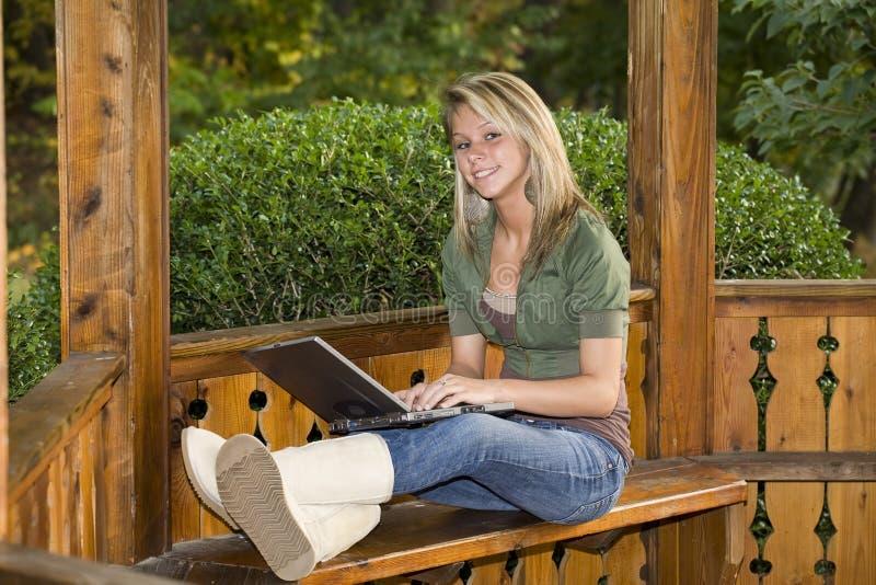 女孩她膝上型计算机公园少年使用 免版税库存照片