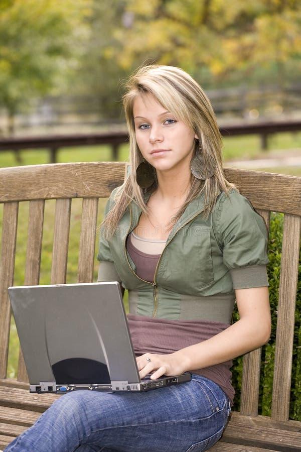 女孩她膝上型计算机公园少年使用 库存照片