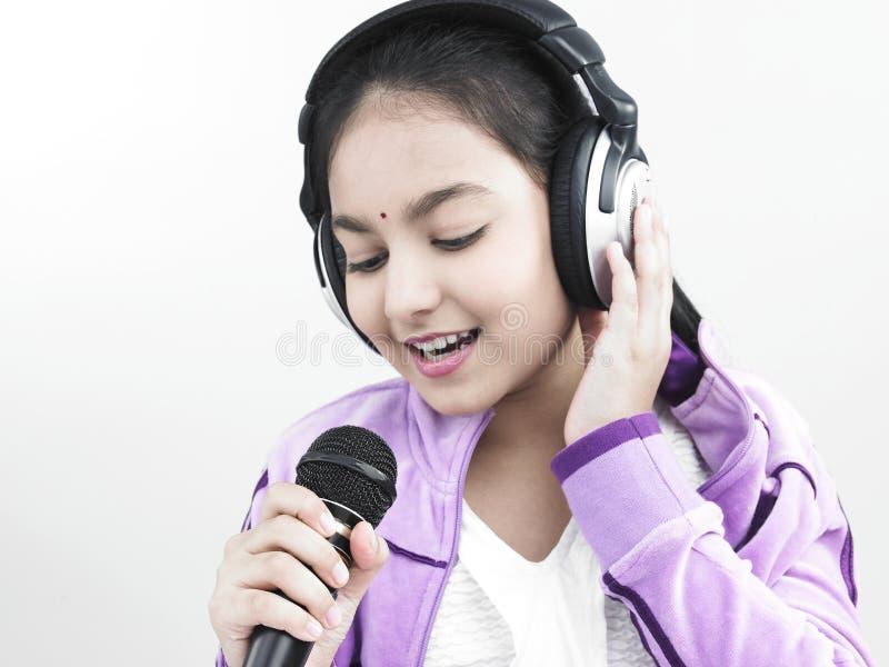 女孩她话筒唱歌 图库摄影