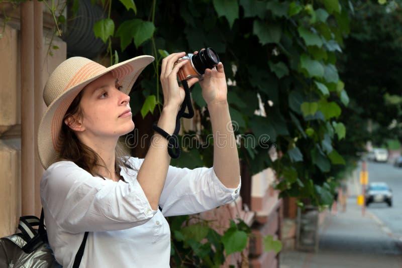 女孩妇女帽子太阳葡萄酒照相机旅行旅游照片照相机射击街道白色乐声牌Lumix 免版税图库摄影