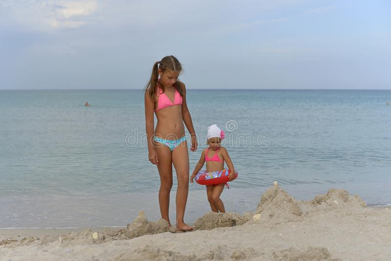 女孩姐妹在沙滩的比基尼泳装站立在一个夏日 免版税库存照片