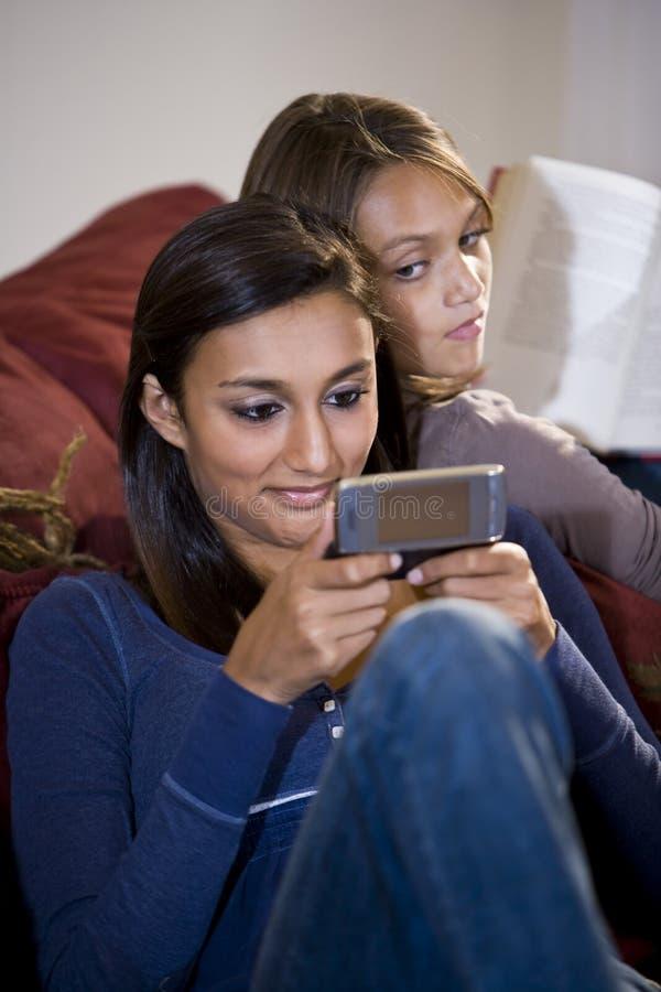 女孩姐妹少年texting的手表 免版税库存照片