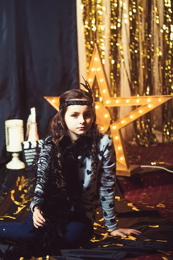 女孩姿势减速火箭的样式时尚和女用长围巾 逗人喜爱的儿童女演员在影片或戏院演播室,葡萄酒 减速火箭或 库存照片