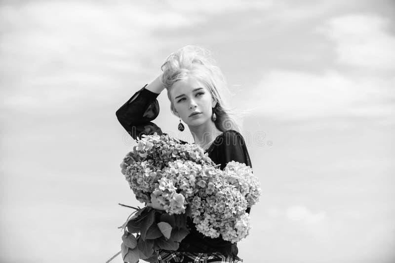 女孩嫩白肤金发的举行八仙花属花束 i 精美妇女的柔和的花 ? 图库摄影