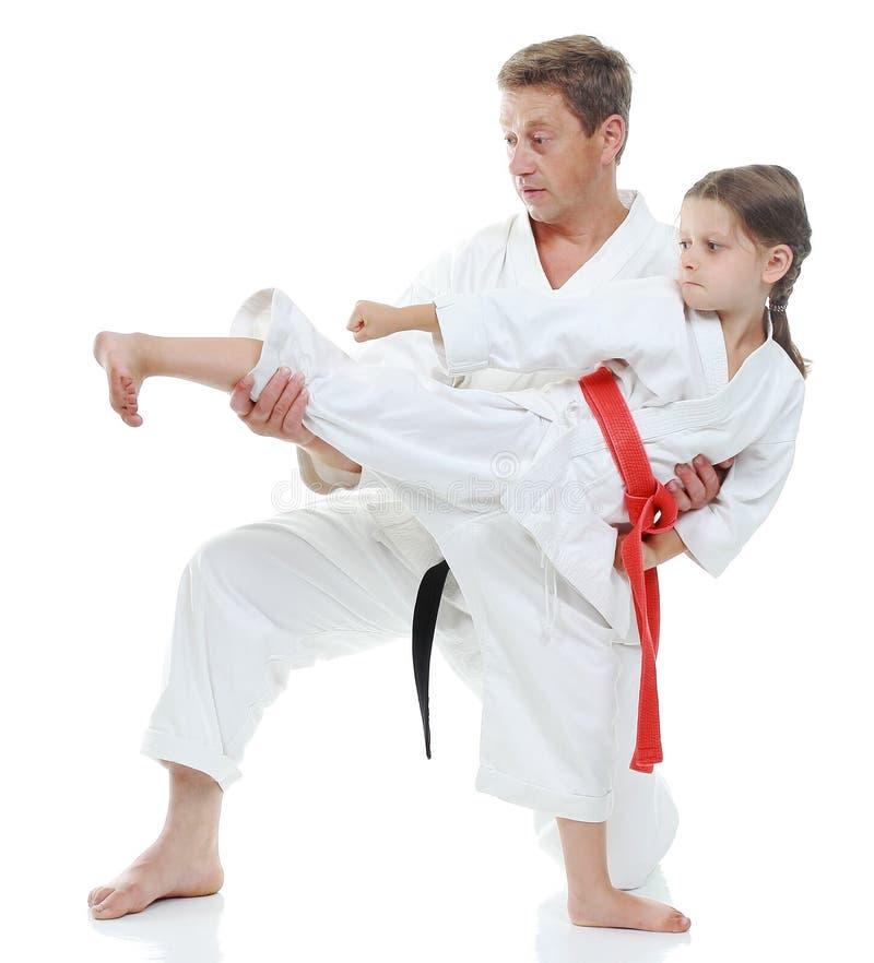 女孩学会打在白色背景的反撞力腿 图库摄影