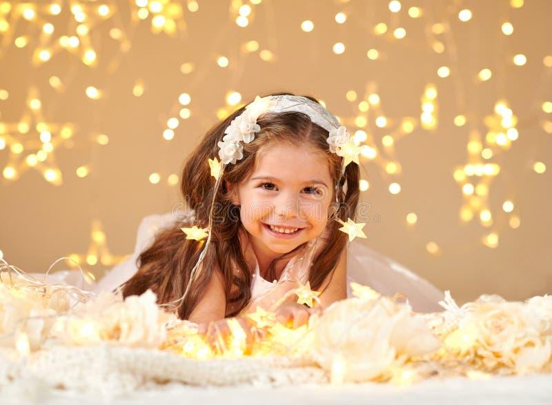 女孩孩子使用与圣诞灯,黄色背景,桃红色礼服 免版税图库摄影