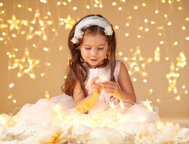 女孩孩子使用与圣诞灯,黄色背景,桃红色礼服 免版税库存照片