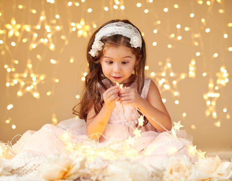 女孩孩子使用与圣诞灯,黄色背景,穿戴在桃红色礼服 她在星光看 免版税库存照片