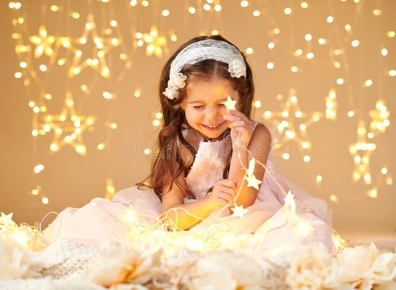 女孩孩子使用与圣诞灯,黄色背景,穿戴在桃红色礼服 她在星光看 免版税库存图片
