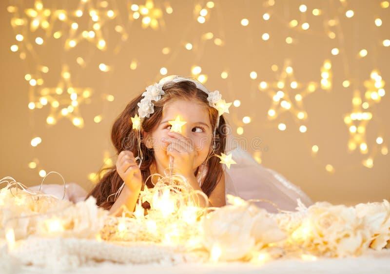 女孩孩子使用与圣诞灯,黄色背景,穿戴在桃红色礼服 她在星光看 库存照片