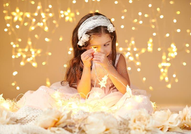 女孩孩子使用与圣诞灯,黄色背景,穿戴在桃红色礼服 她在星光看 图库摄影