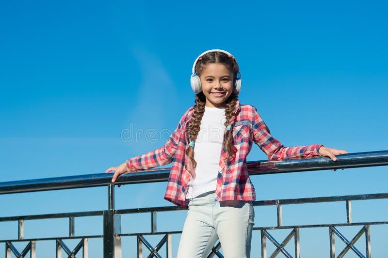 女孩孩子听音乐户外与现代耳机 享受音乐到处 该当a听的最佳的音乐应用程序 库存照片