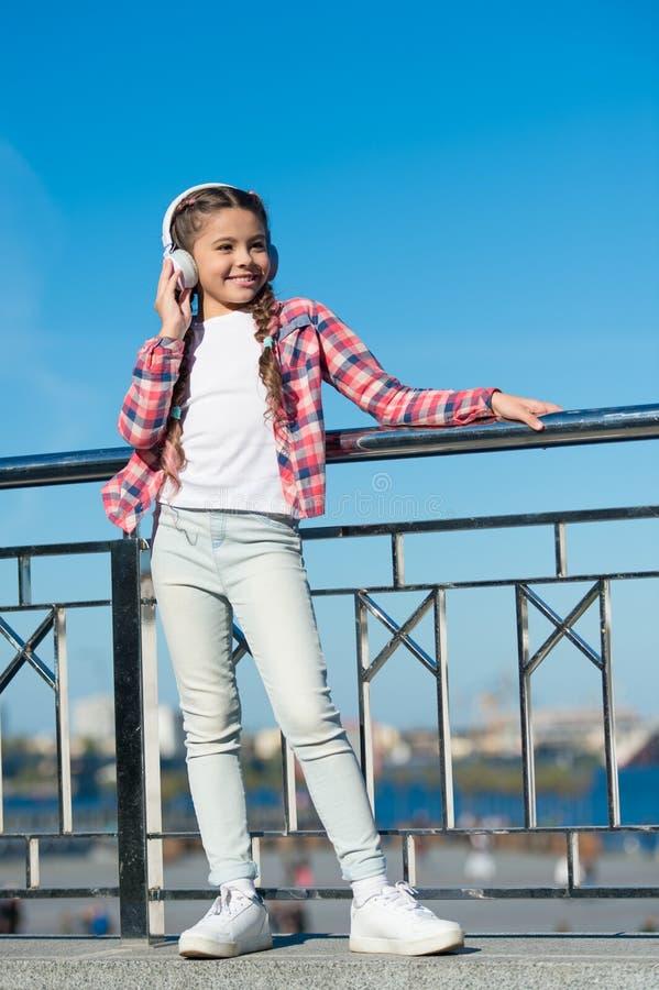 女孩孩子听音乐户外与现代耳机 孩子耳机测试了并且排列了最好对最坏享受声音 库存照片