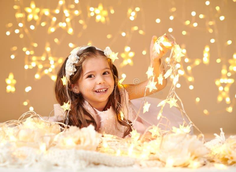 女孩孩子摆在与圣诞灯,黄色背景,桃红色礼服 免版税库存图片