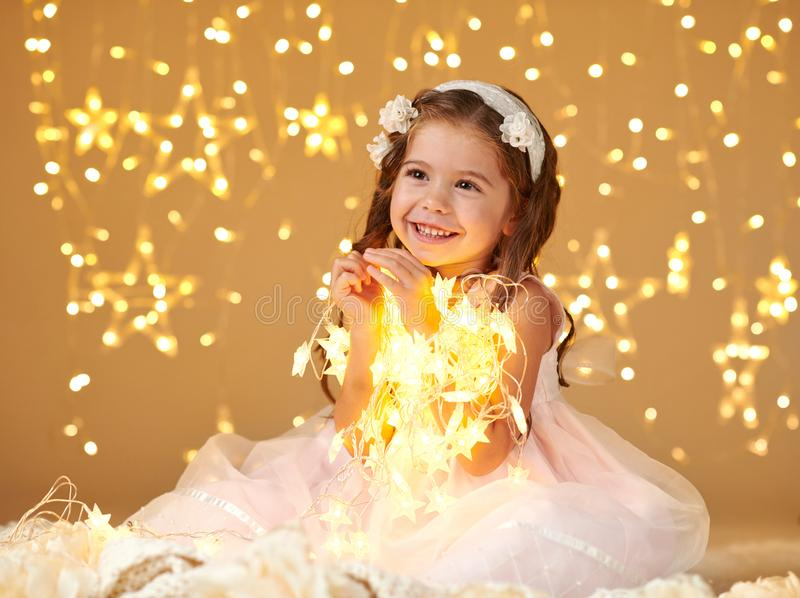 女孩孩子摆在与圣诞灯,黄色背景,桃红色礼服 图库摄影