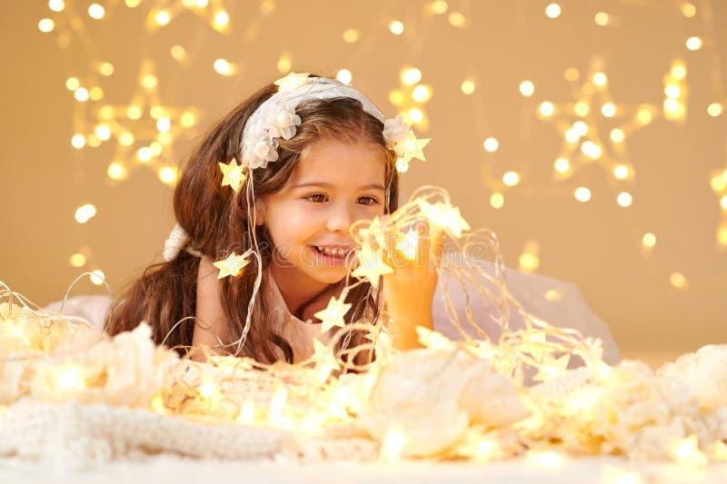 女孩孩子摆在与圣诞灯,黄色背景,桃红色礼服 免版税库存照片