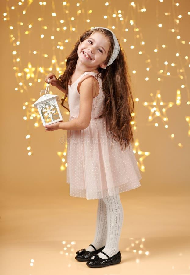 女孩孩子摆在与在圣诞灯的灯笼,黄色背景,桃红色礼服 免版税库存照片