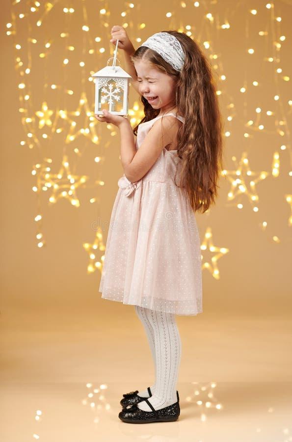 女孩孩子摆在与在圣诞灯的灯笼,黄色背景,桃红色礼服 库存照片