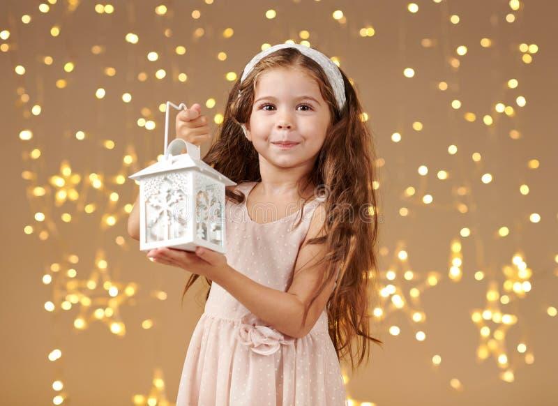 女孩孩子摆在与在圣诞灯的灯笼,黄色背景,桃红色礼服 图库摄影