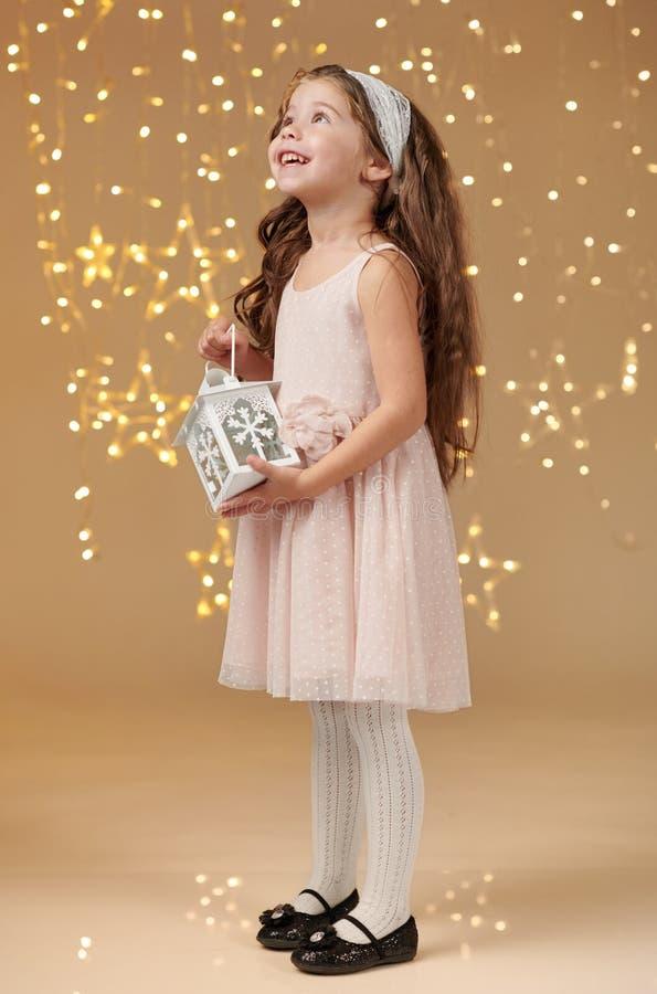 女孩孩子摆在与在圣诞灯的灯笼,黄色背景,桃红色礼服 库存图片