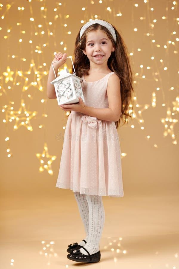 女孩孩子摆在与在圣诞灯的灯笼,黄色背景,桃红色礼服 免版税库存图片