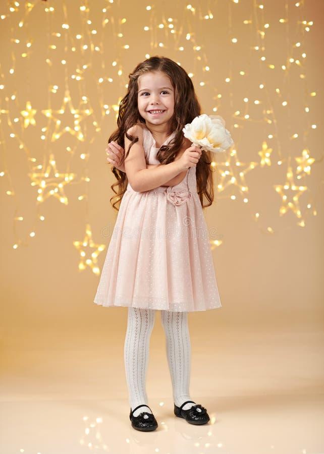 女孩孩子是在圣诞灯,黄色背景,桃红色礼服 库存图片