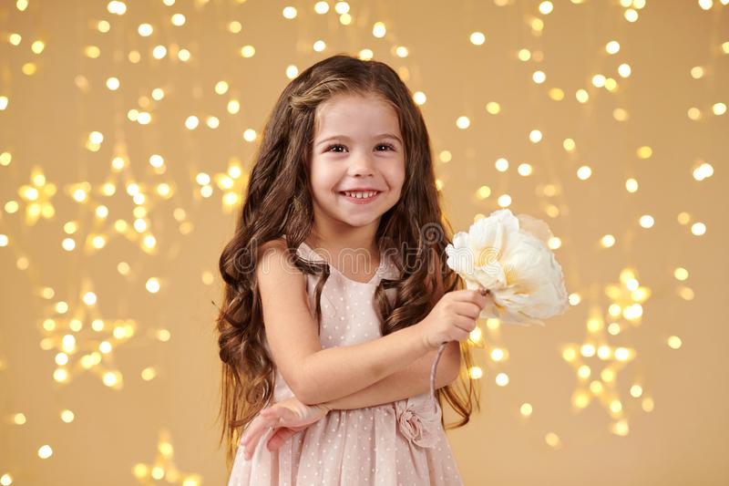女孩孩子是在圣诞灯,黄色背景,桃红色礼服 免版税库存图片