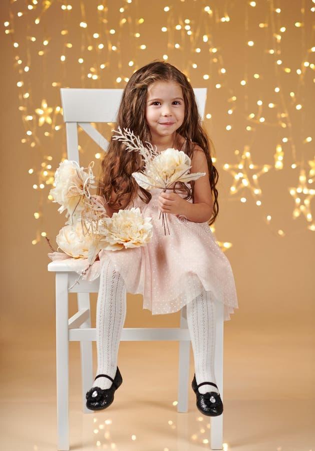 女孩孩子是在圣诞灯,黄色背景,桃红色礼服 免版税图库摄影
