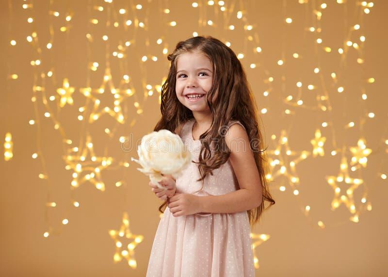 女孩孩子是在圣诞灯,黄色背景,桃红色礼服 图库摄影
