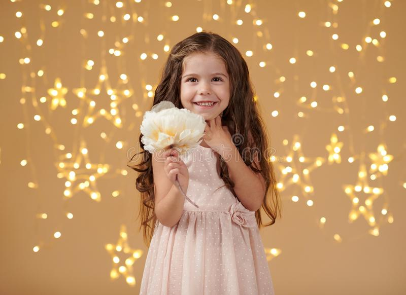 女孩孩子是在圣诞灯,黄色背景,桃红色礼服 免版税库存照片
