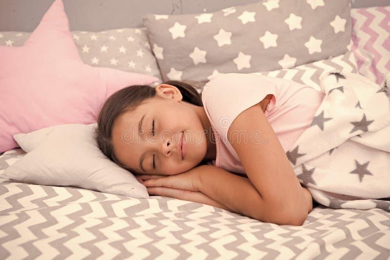 女孩孩子睡着在枕头 睡眠的质量取决于许多因素 选择适当的枕头很好睡觉 女孩放置 免版税图库摄影