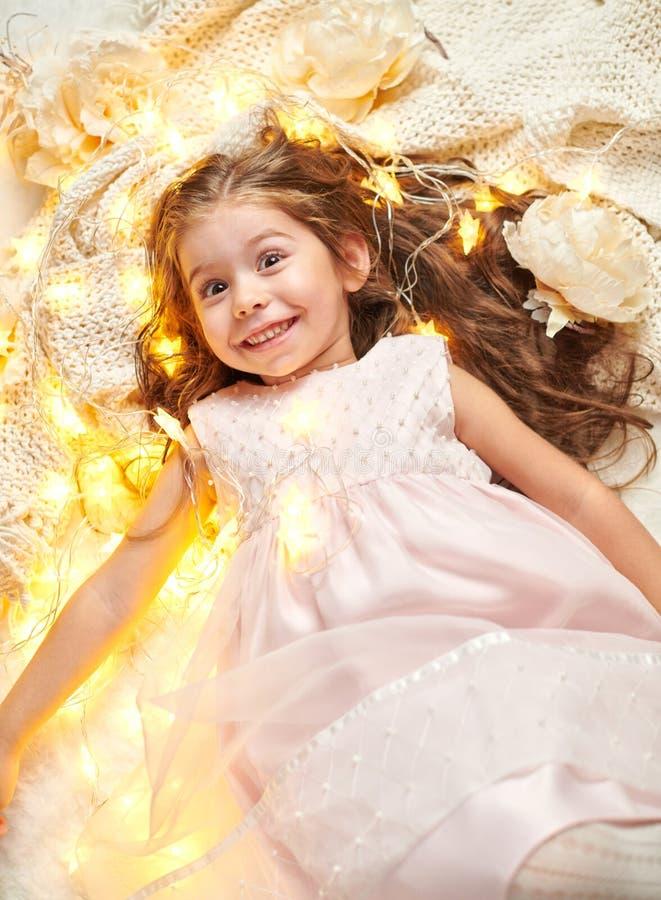 女孩孩子说谎与圣诞灯和花,面孔特写镜头 免版税图库摄影