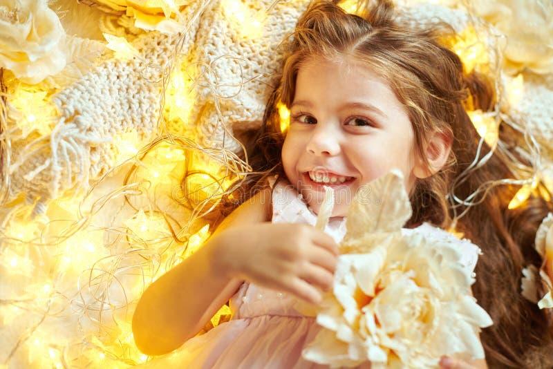 女孩孩子说谎与圣诞灯和花,面孔特写镜头 免版税库存图片