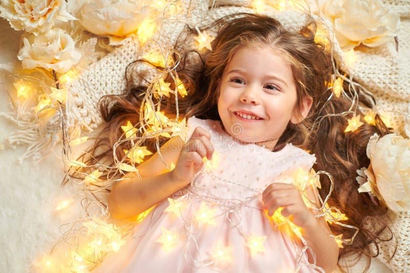 女孩孩子说谎与圣诞灯和花,面孔特写镜头 库存照片