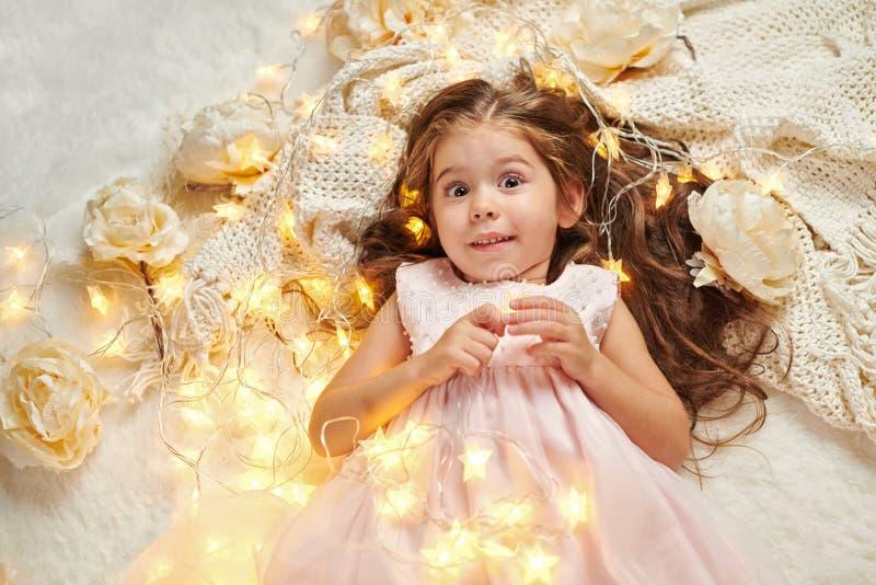 女孩孩子说谎与圣诞灯和花,面孔特写镜头 免版税库存照片