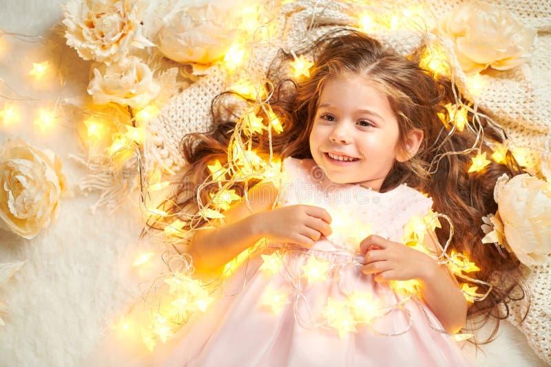 女孩孩子说谎与圣诞灯和花,面孔特写镜头 库存图片