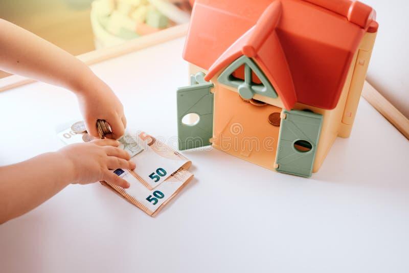 女孩孩子,插入物硬币到存放框,在白色背景储蓄照片的攒钱概念 免版税图库摄影