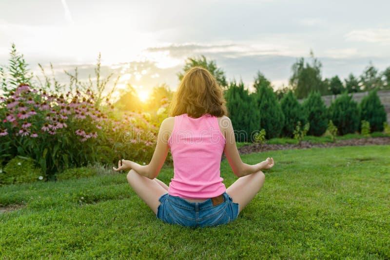 女孩实践的瑜伽,思考在夏天日落背景,在绿草,草坪在房子附近 库存照片