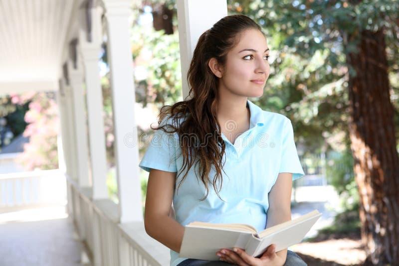 女孩家庭门廊俏丽的读取 免版税库存图片