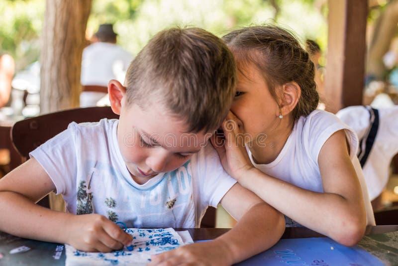 女孩对一个俏丽的男孩耳语某事在街道餐馆 免版税库存照片