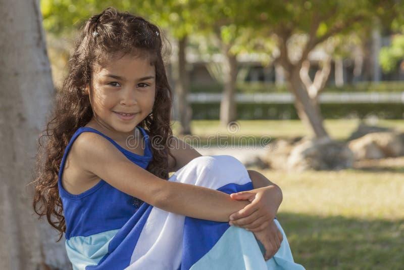 女孩对照相机微笑用她的被包裹的膝盖倾向手坐她的腿 免版税图库摄影