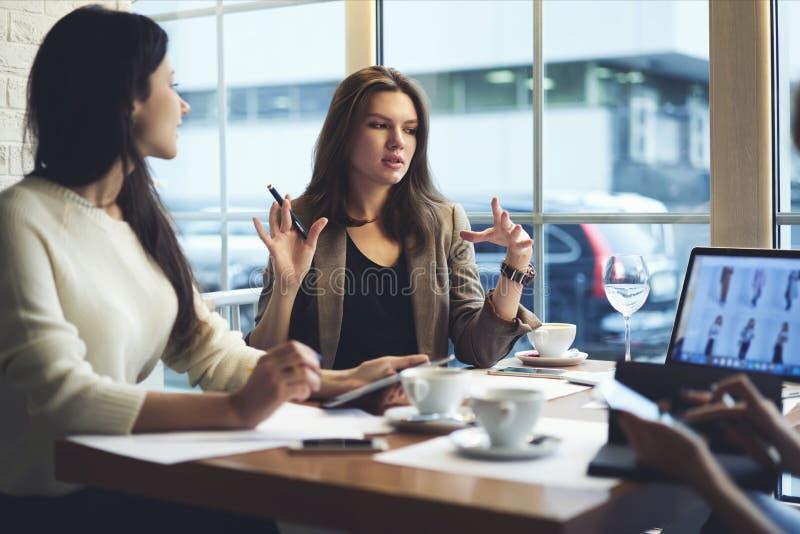 女孩对网上网商店的名牌服装,当有会见同事在咖啡馆时 库存照片