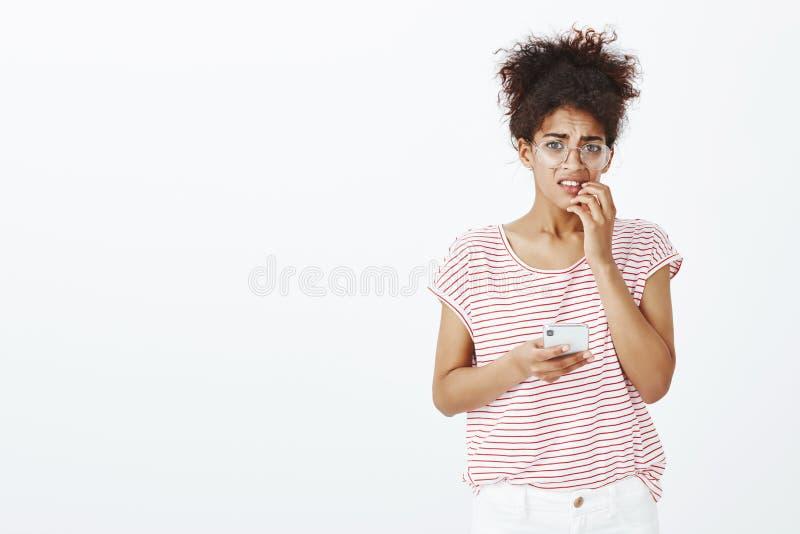女孩对错误人的传送的信息 玻璃和时髦成套装备的,尖酸的指甲盖急切不快乐的深色皮肤的妇女 库存照片