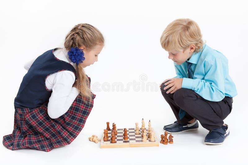 女孩封死男孩,下棋,被隔绝的白色背景的制服的学童 免版税库存照片