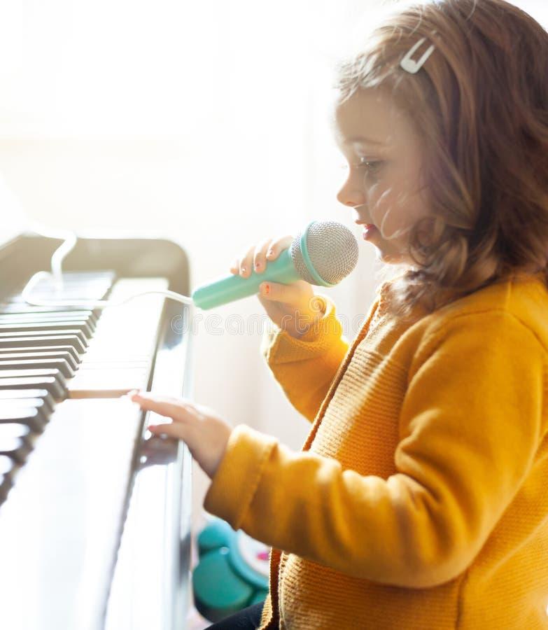女孩小孩使用与钢琴和玩具话筒 免版税库存照片